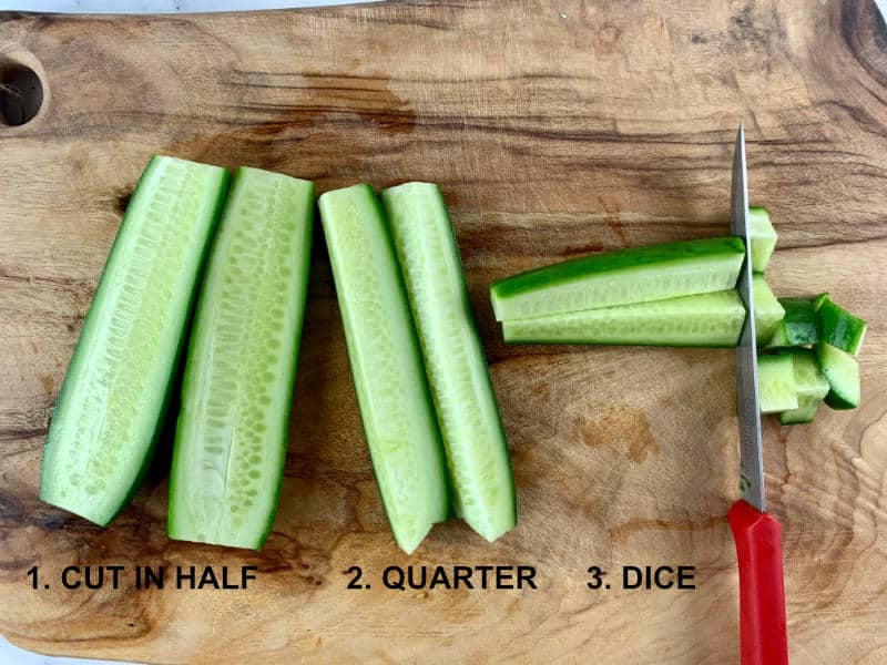 CUTTING CUCUMBERS ON A WOODEN BOARD WITH A KNIFE