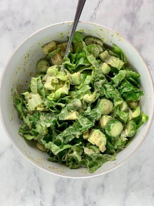 TOSSING ROMAINE AVOCADO SALAD WITH DRESSING IN BOWL