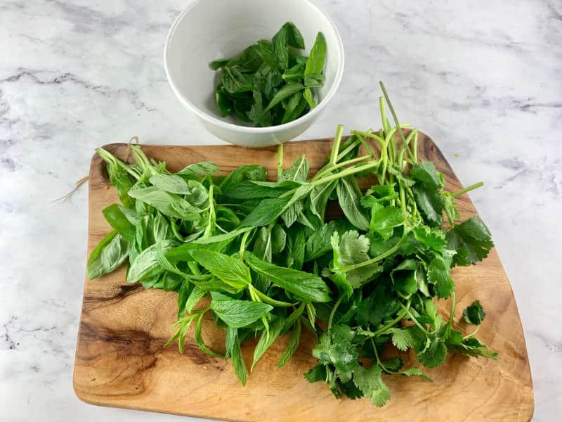 PICKING BASIL, VIETNAMESE MINT & CORIANDER LEAVES FROM STEMS ON WOOODEN BAORD WITH WHITE BOWL IN BACKGROUND FROM STEMS