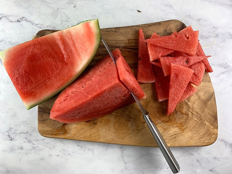 1-OVERHEAD-VEIW-OF-SLICING-WATERMELON ON A WOODEN BOARD WITH A KNIFE