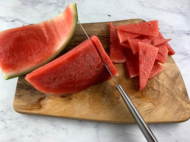 SLICING WATERMELON INTO TRIANGLES ON A WOODEN BOARD WITH A KNIFE