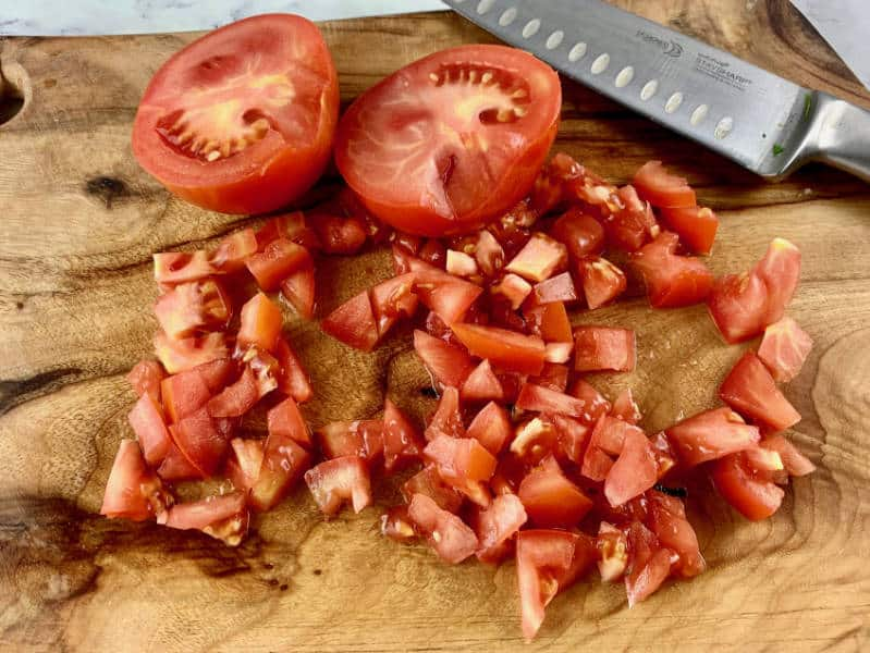 DICING TOMATOES ON A WOODEN BOARD WITH A KNIFE