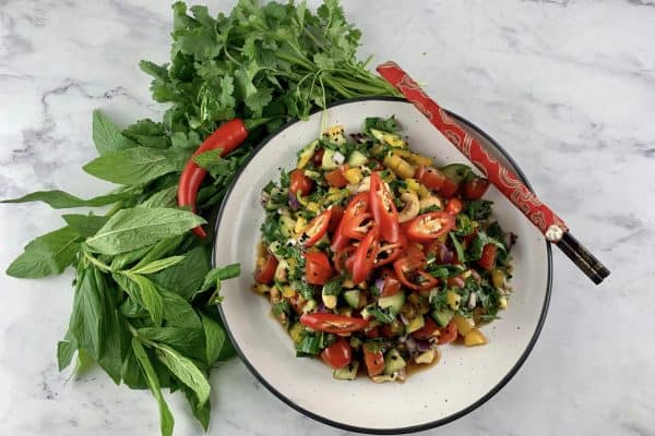 ASIAN CHOPPED SALAD ON A WHITE PLATE WITH FRESH HERBS, CHILLI & CHOPSTICKS
