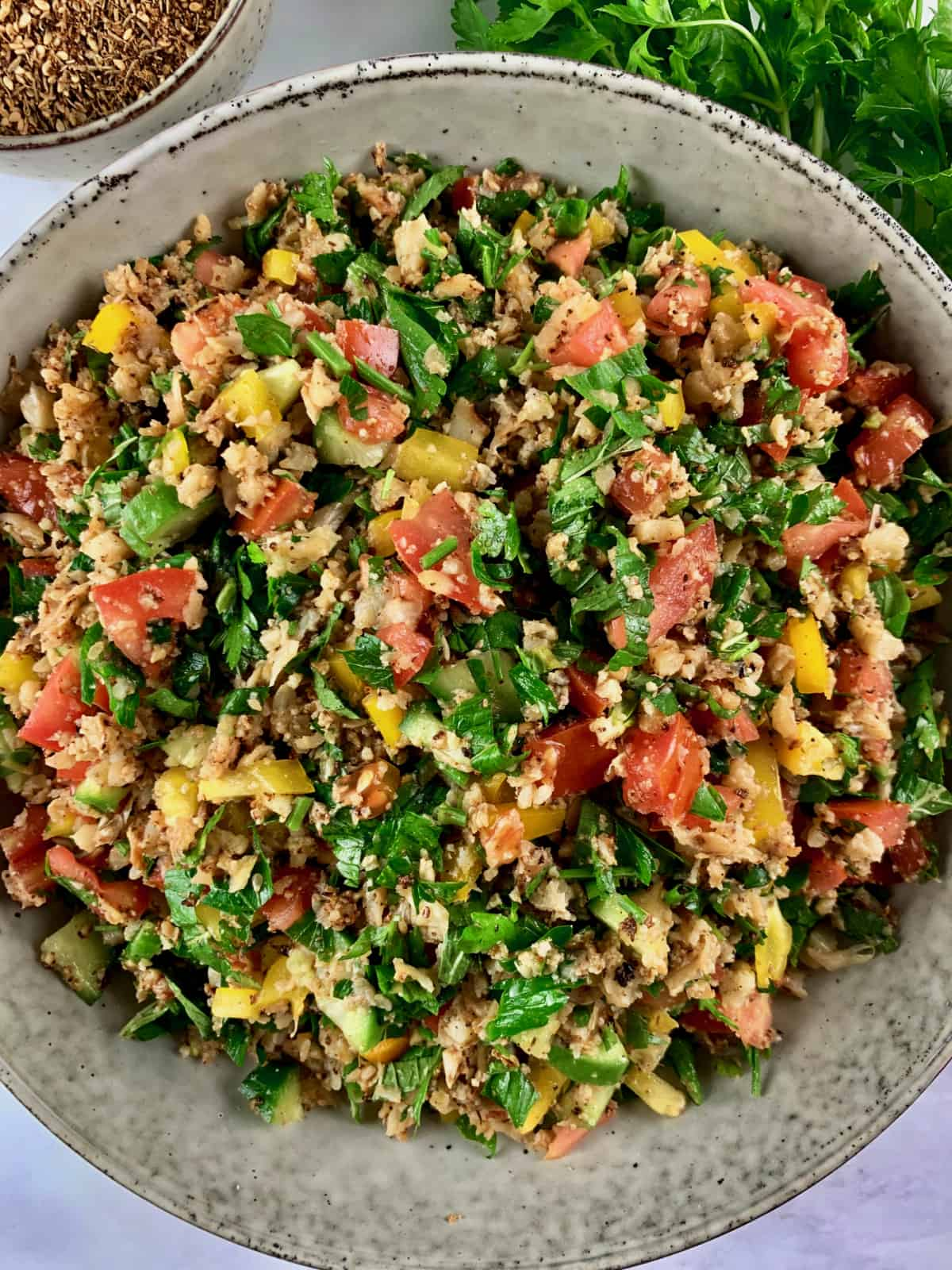CAULIFLOWER TABBOULEH IN A BOWL WITH ZA'ATAR AND PARSLEY ON THE SIDE