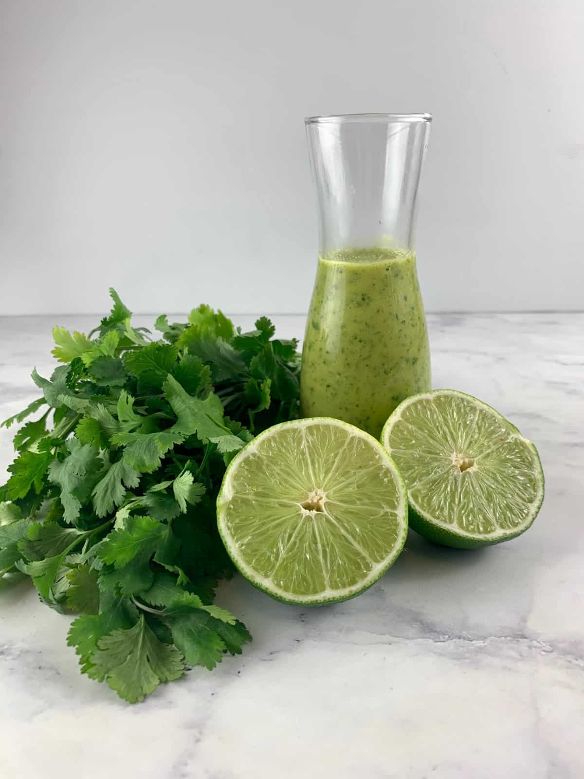 CILANTRO LIME DRESSING IN A GLASS. BOTTLE WITH CILANTRO AND CUT LIMES
