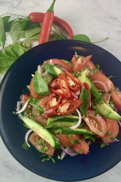 KACHUMBER SALAD ON A NAVY BLUE PLATE WITH CURRY LEAVES AND CHILLIS IN LANDSCAPE