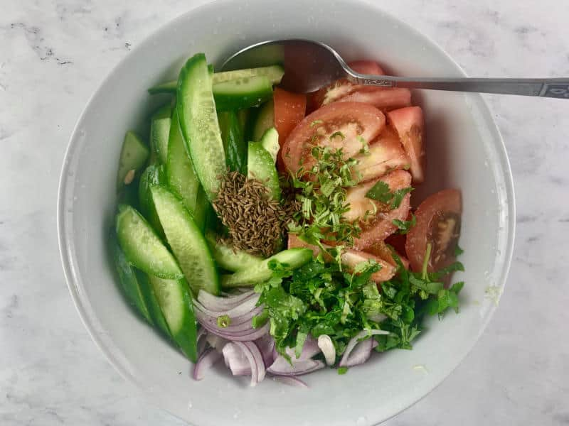 KACHUMBER SALAD INGREDIENTS IN WHITE BOWL WITH SPOON