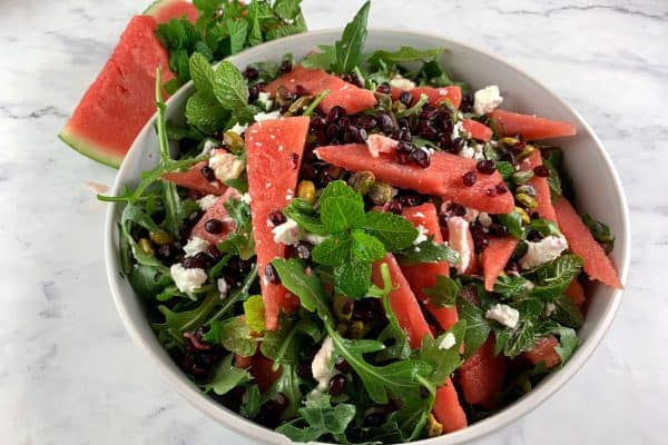 PERSIAN WATERMELON & FETA SALAD IN A WHITE BOWL WITH WATERMELON SLICES & MINT ON THE SIDE