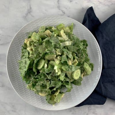 ROMAINE AVOCADO SALAD WITH VEGAN CAESAR DRESSING ON WHITE PLATTER WITH NAVY LINEN NAPKIN