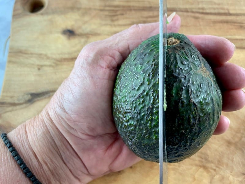 SLICING AROUND AN AVOCADO WITH A KNIFE ON A WOODEN BOARD