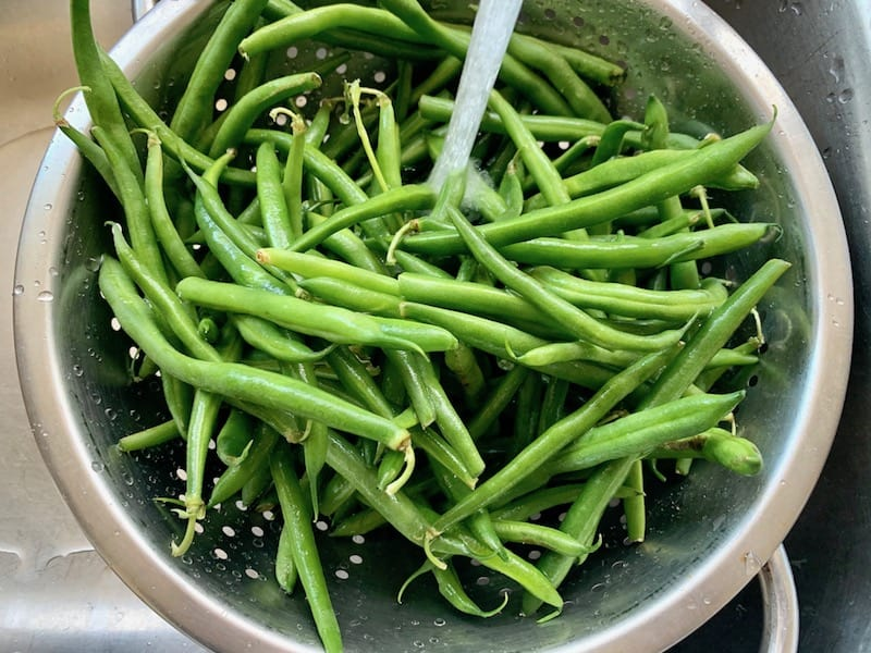 WASHING GREEN BEANS IN A COLANDER UNDER COLD RUNNING WATER