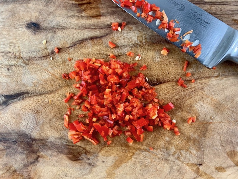 FINELY DICING CHILLI WITH A KNIFE ON WOODEN BOARD