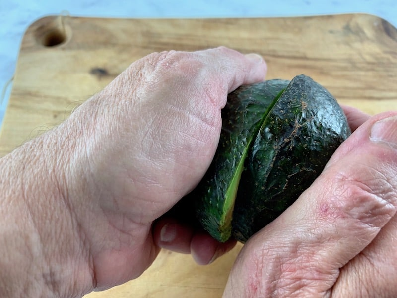 HANDS TWISTING AN AVOCADO ON A WOODEN BOARD