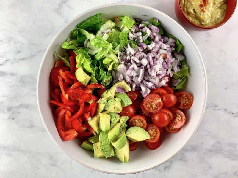 AVOCADO RANCH SALAD INGREDIENTS IN A BOWL WITH AVOCADO RANCH ON THE SIDE