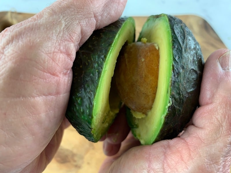 HANDS PULLING APART AN AVOCADO TO REVEAL SEED