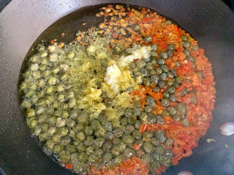 ADDING LEMON ZEST, CAPERS, GARLIC & CHILLI TO HOT PAN WITH OIL