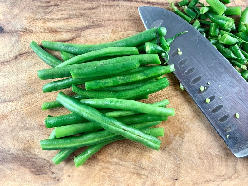 CUTTING OTHER SIDE OF GREEN BEAN ENDS ON A WOODEN BOARD WITH A KNIFE