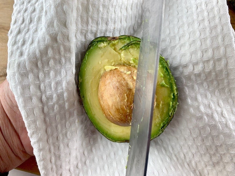 KNIFE HACKING INTO AN AVOCADO SEED IN A TEATOWEL