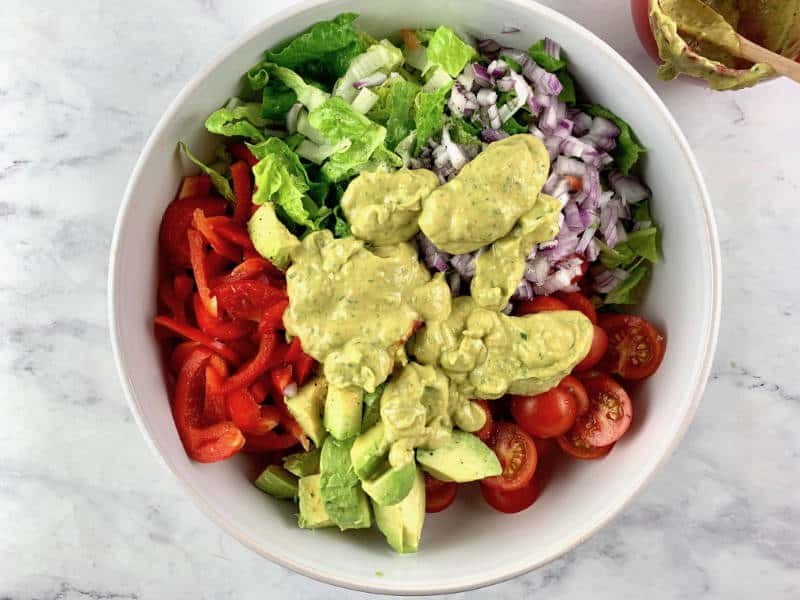 AVOCADO RANCH SALAD INGREDIENTS WITH DRESSING ON TOP
