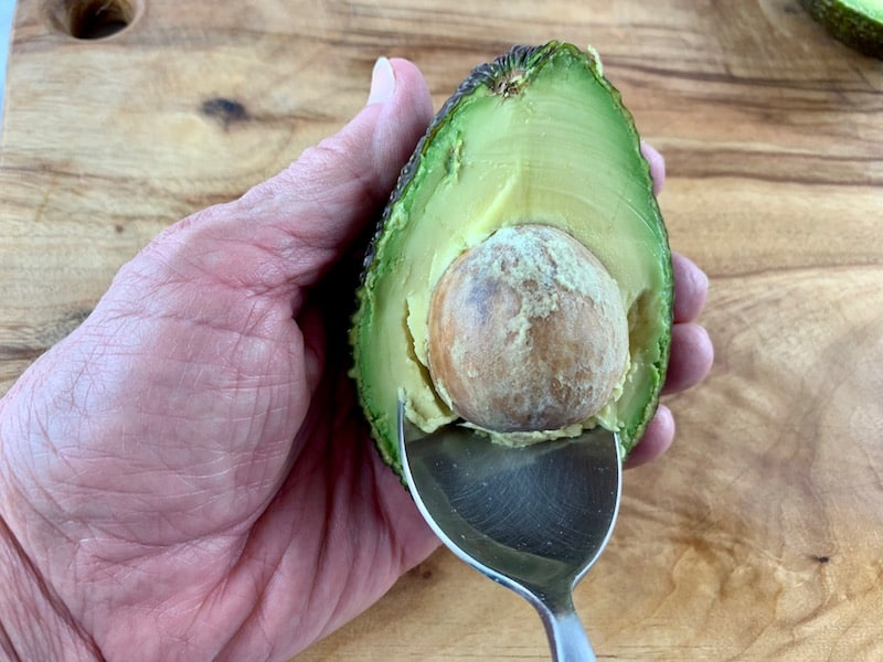 USING A SPOON TO REMOVE AVOCADO SEED