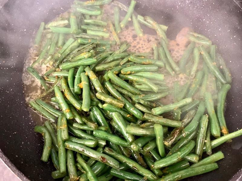 ADDING ORANGE & LEMON JUICE TO SAUTÉED GREEN BEANS IN PAN