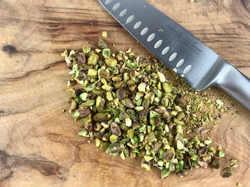 CHOPPED PISTACHIOS ON A WOODEN BOARD WITH A KNIFE