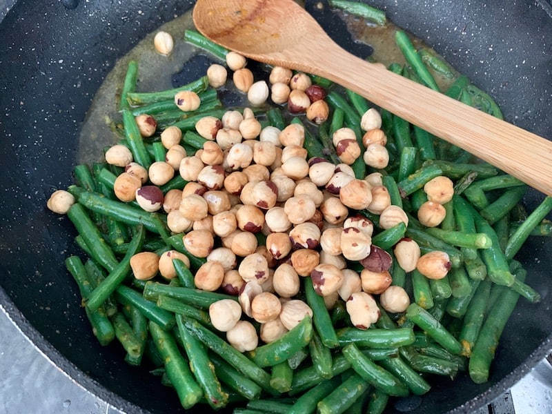 ADDING ROASTED HAZELNUTS TO GREEN BEAN PAN