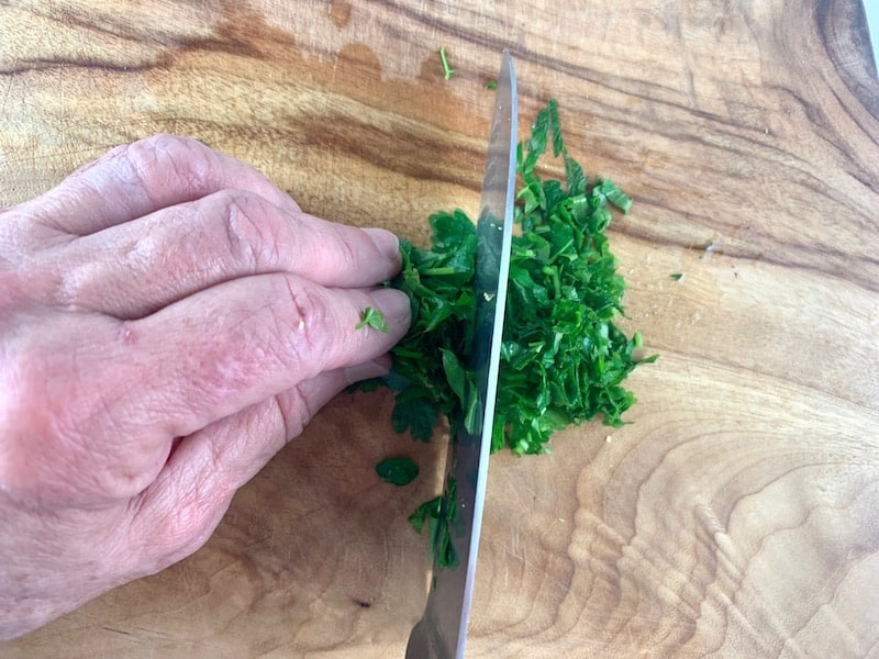 HANDS CHOPPING PARSLEY ON A WOODEN BOARD WITH A KNIFE