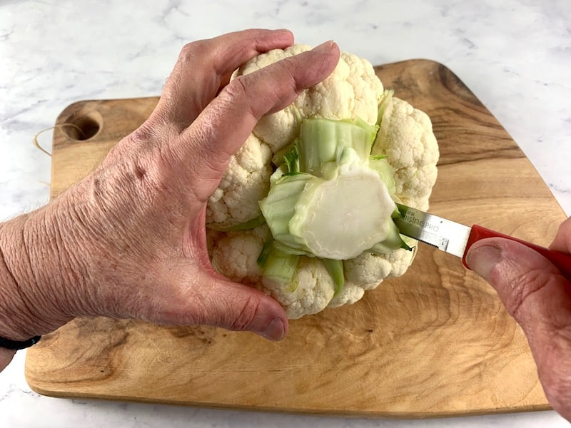 HANDS CUTTING THE STEM FROM A CAULIFLOWER ON WOODEN BOARD