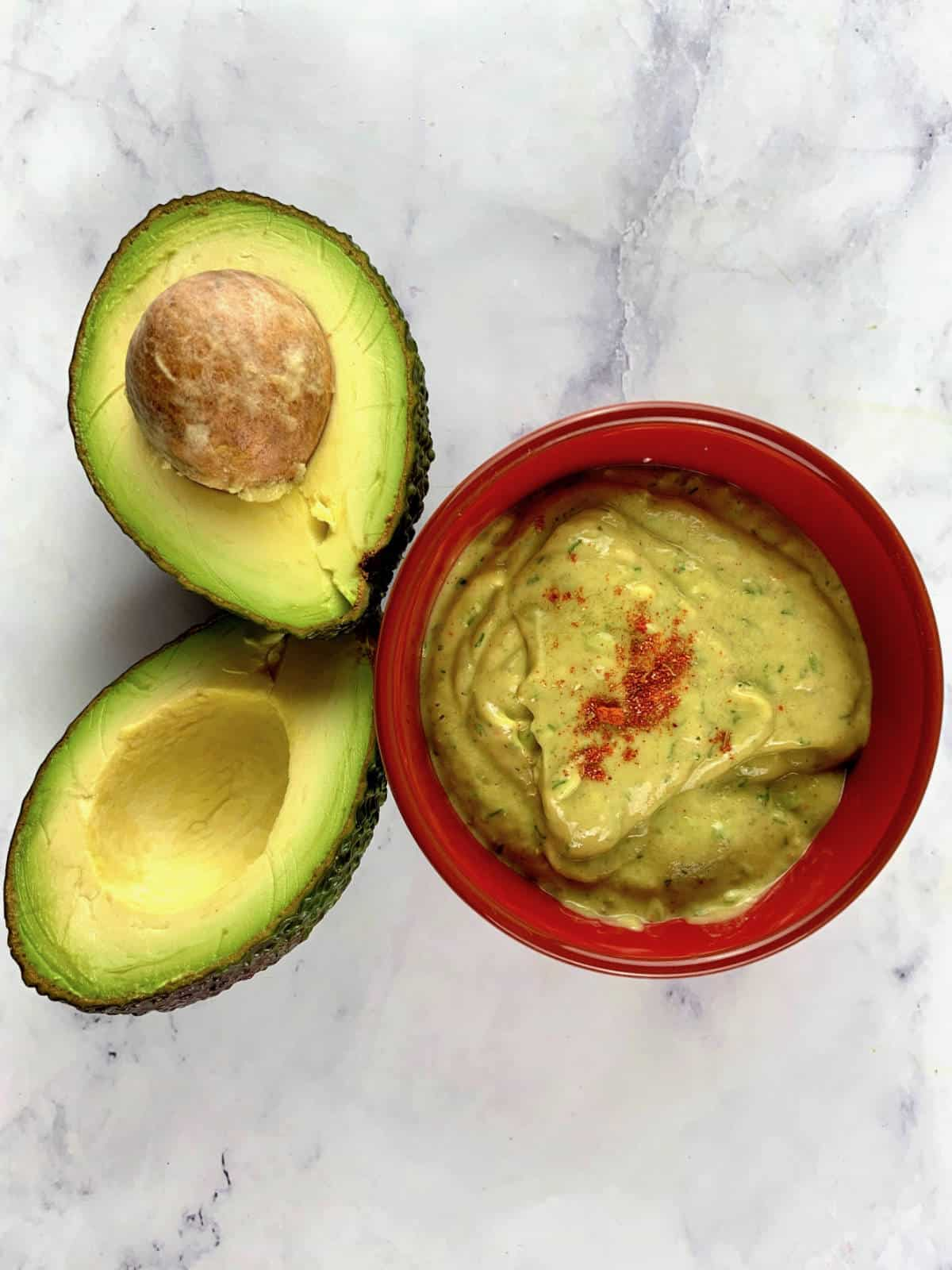 AVOCADO RANCH DRESSING IN RED BOWL WITH AVOCADOS ON THE SIDE