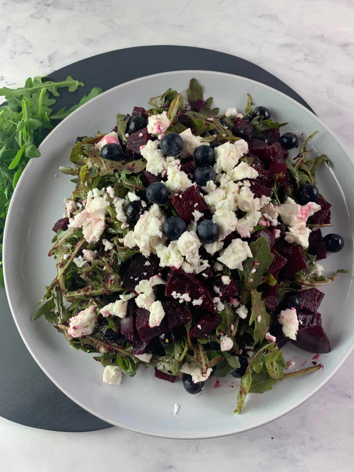 Red white and blue salad in portrait with beets, blueberries, feta and arugula