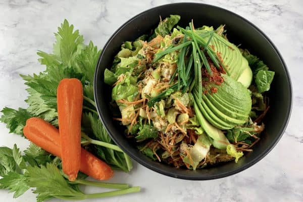 CANNED SALMON SALAD IN A BLACK BOWL WITH CELERY LEAVES AND CARROTS ON THE SIDE