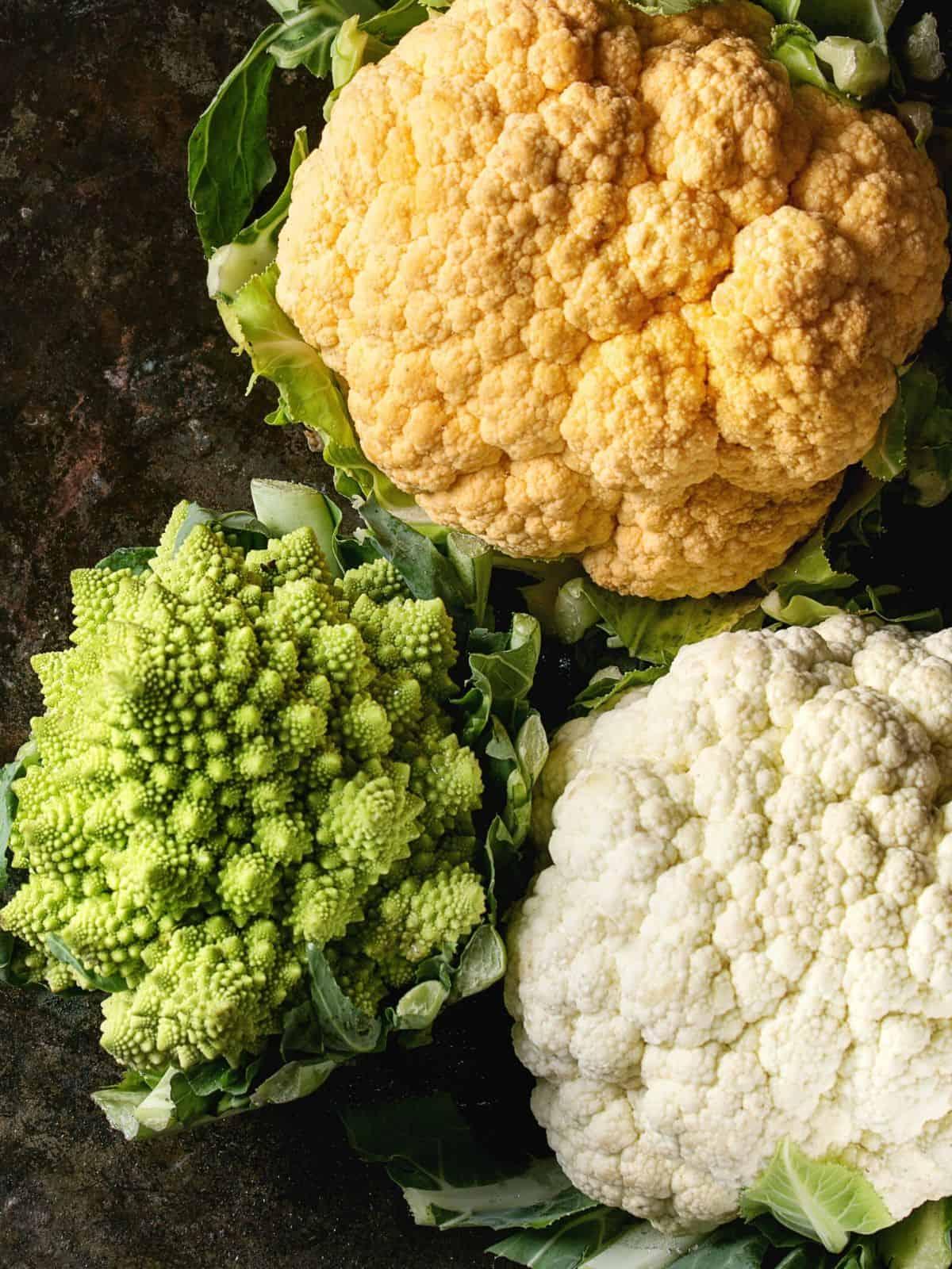 white, orange & romanesco cauliflower on a dark background
