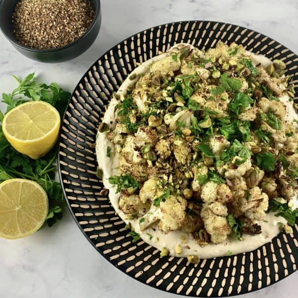 CAULIFLOWER TAHINI SALAD ON A BLACK PATTERNED PLATE WITH ZA'ATAR AND LEMONS & PARSLEY ON THE SIDE