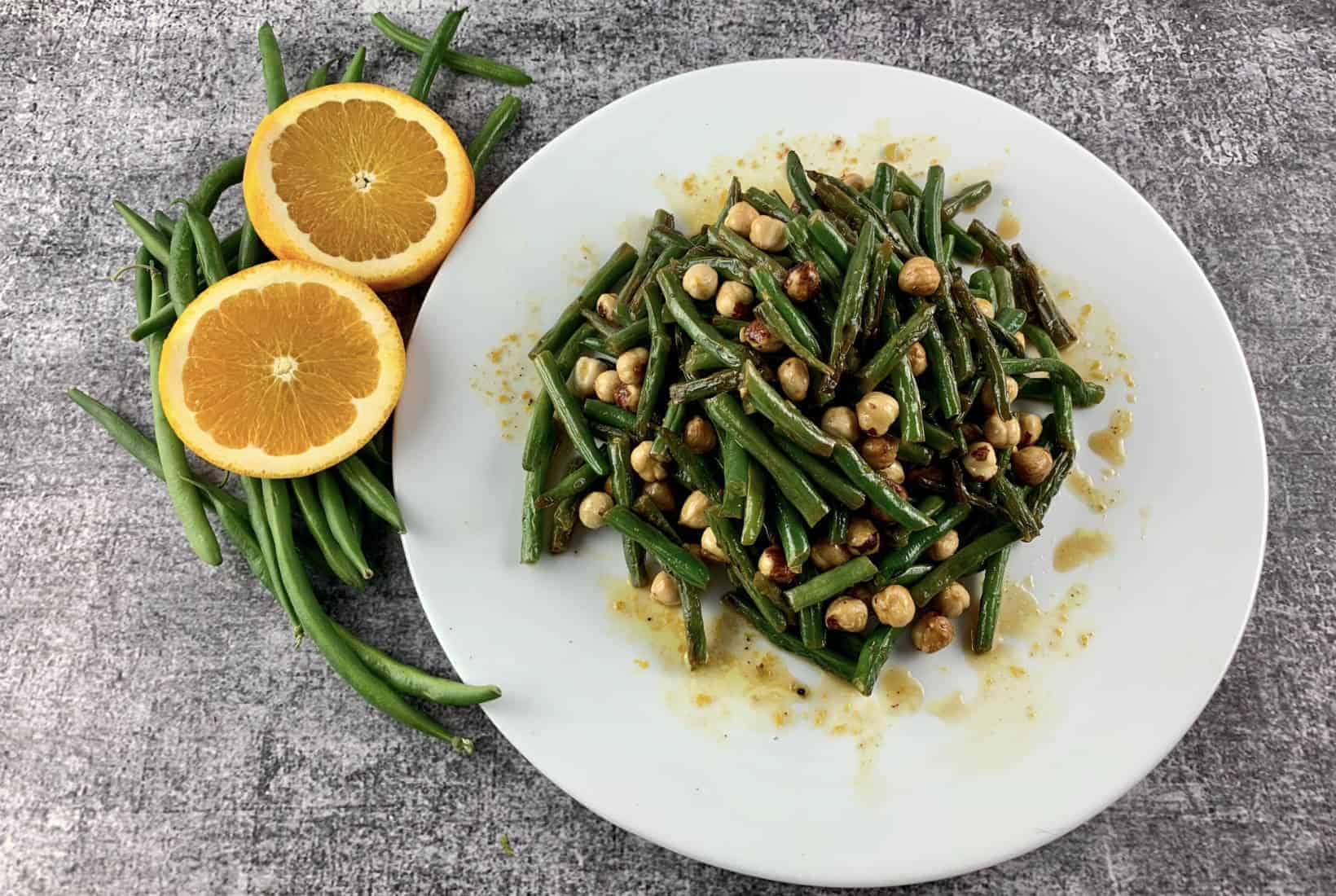 GREEN BEAN SALAD WITH ORANGE AND HAZELNUTS IN A WHITE PLATTER WITH ORANGE SLICES & BEANS ON THE SIDE