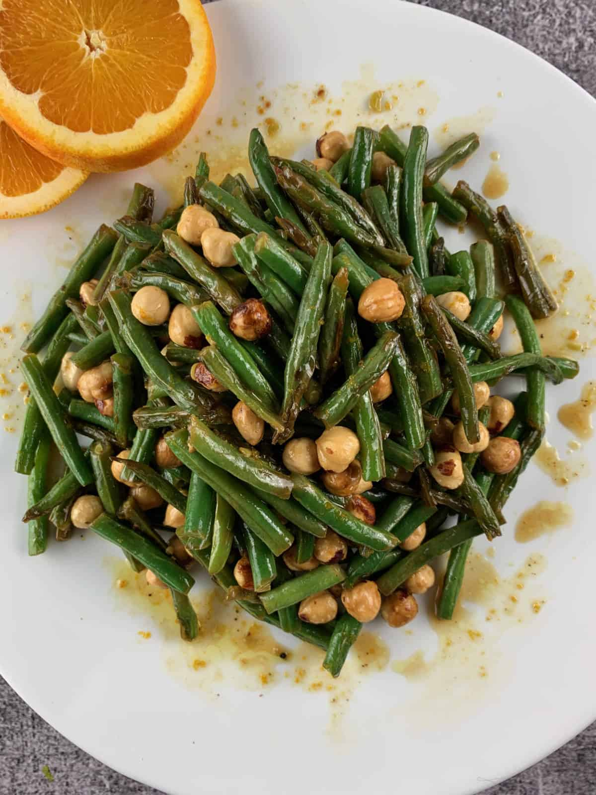 GREEN BEAN SALAD WITH ORANGE AND HAZELNUTS IN A WHITE PLATTER WITH ORANGE SLICES ON THE SIDE