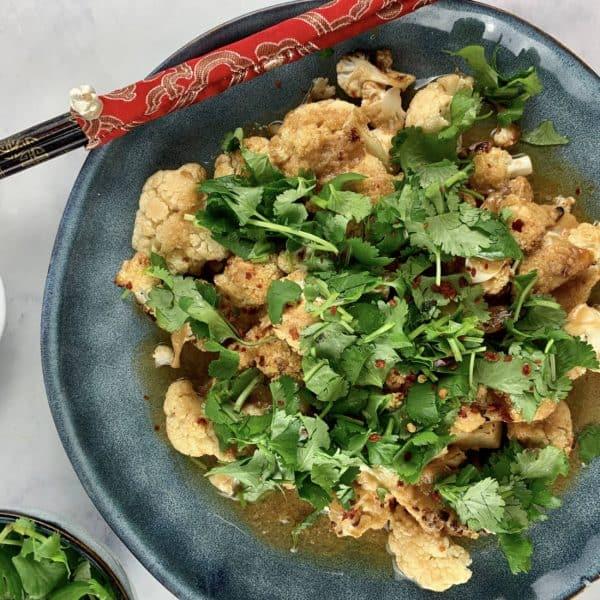 MISO CAULIFLOWER IN BLUE BOWL WITH CHOPSTICKS, CHILLI FLAKES & CORIANDER ON THE SIDE