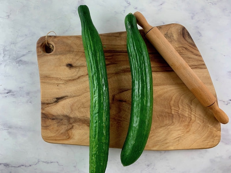 LONG TELEGRAPH CUCUMBERS ON WOODEN BOARD WITH ROLLING PIN