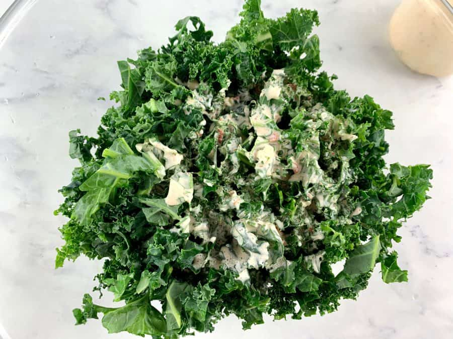 DRESSING POURED OVER SHREDDED KALE IN BOWL