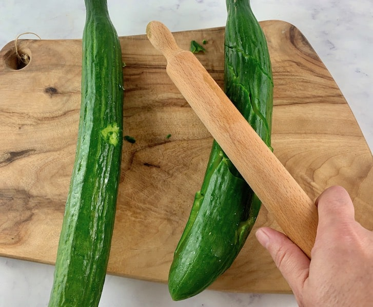 SMASHING CUCUMBERS ON BOARD WITH ROLLING PIN