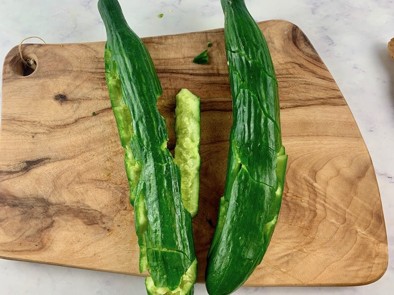 SMASHED CUCUMBERS ON WOODEN BOARD