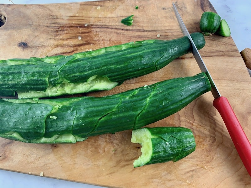 RIMMING SMASHED CUCUMBERS WITH A KNIFE ON A CHOPPING BOARD