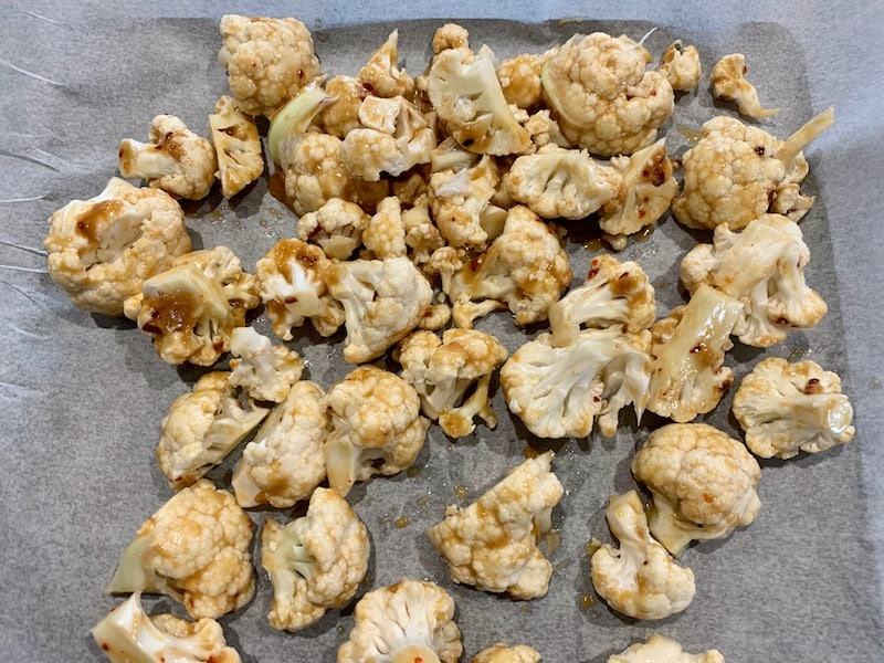 ADDING MARINATED CAULIFLOWER FLORETS TO A LINED BAKING TRAY