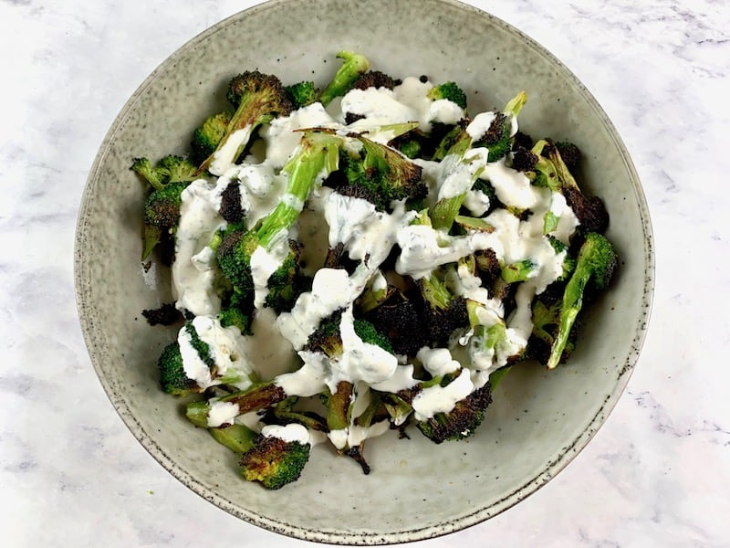 POUR FETA DRESSING OVER CHARRED LOW CARB BROCCOLI