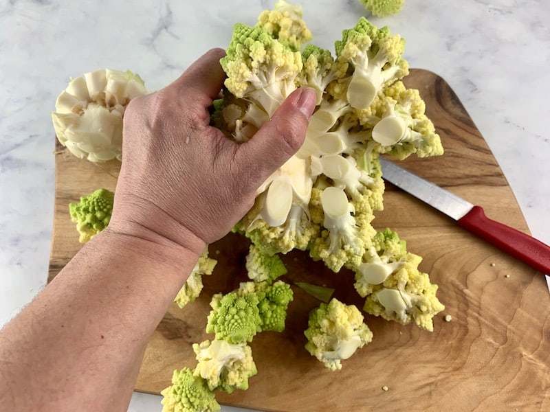 CUTTING ROMANESCO WITH KNIFE ON WOODEN BOARD