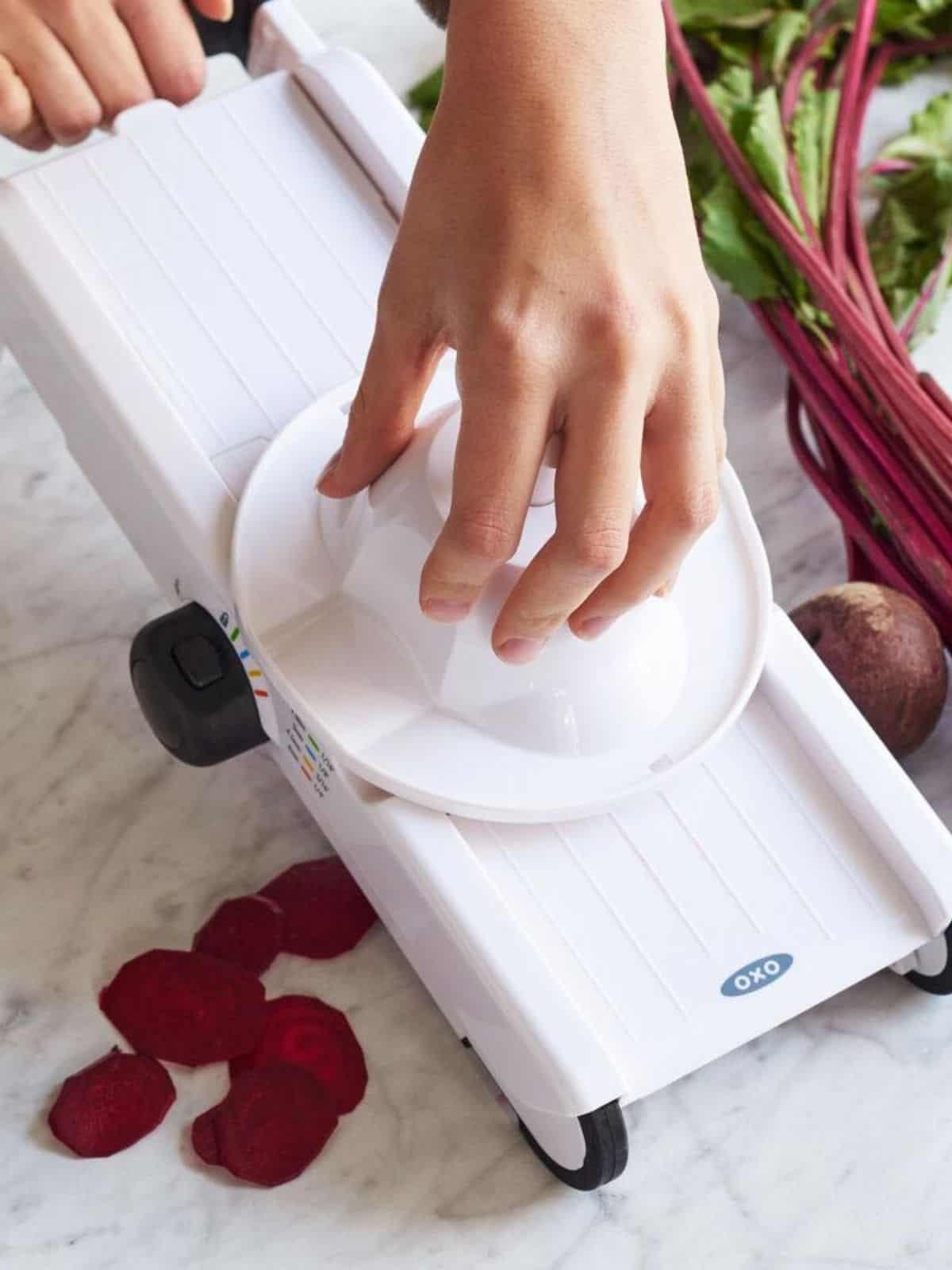 Hands using the best vegetable slicer to slice beets