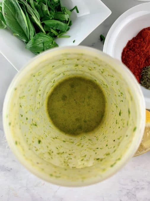 ITALIAN VINAIGRETTE INGREDIENTS BLITZED IN A BLENDER WITH BASIL AND HERBS IN BACKGROUND