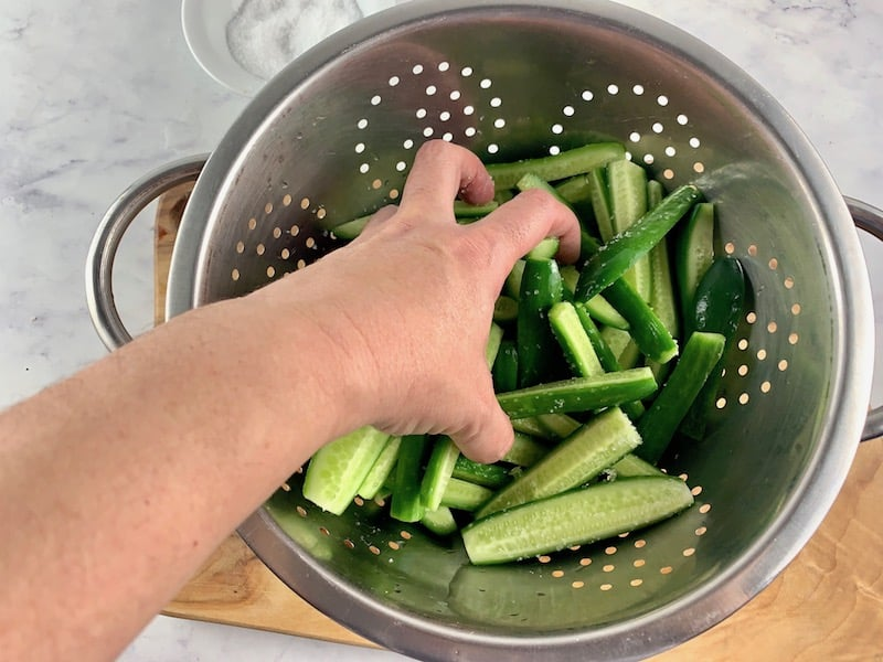 TOSSING SALT THROUGH CUKES IN COLANDER
