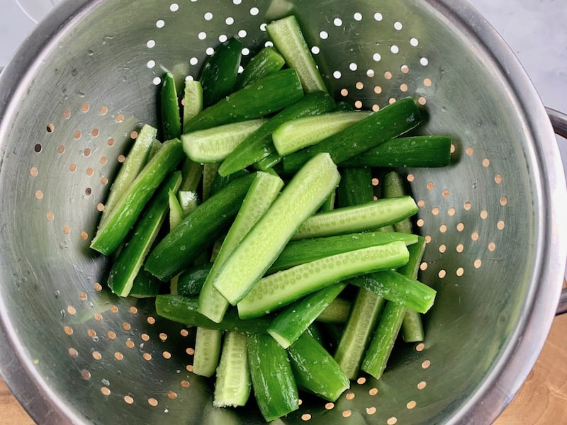 SALTED CUKES IN A STAINLESS STEEL COLANDER