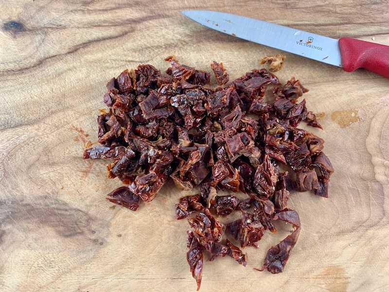 DICING DRIED TOMATOES WITH KNIFE ON WOODEN BOARD